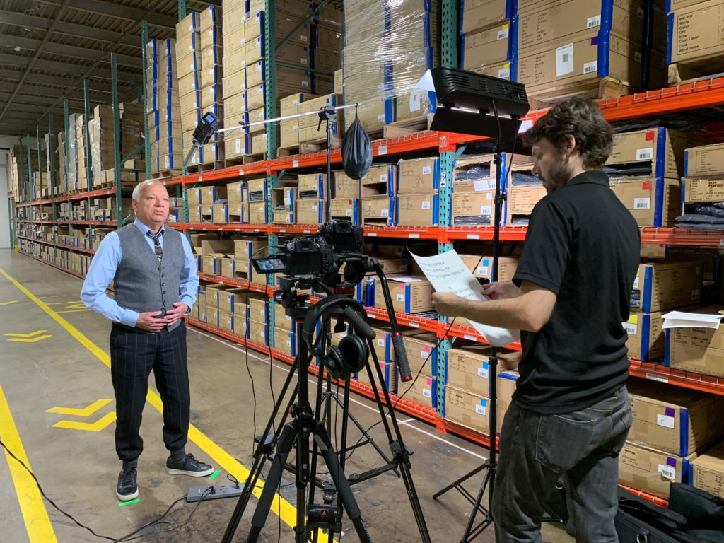 Video Crew filming businessman in warehouse