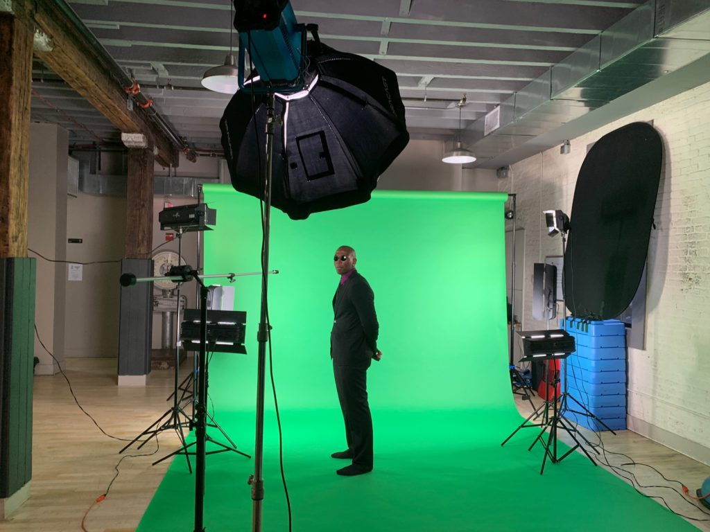 A man in suit filming in front of green screen