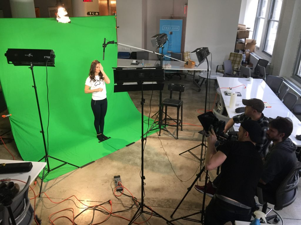 A woman being filmed in front of green screen for video marketing