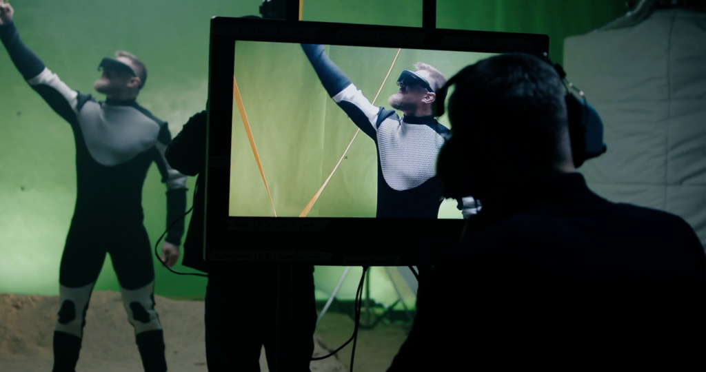 Actor and film crew working in front of a green screen