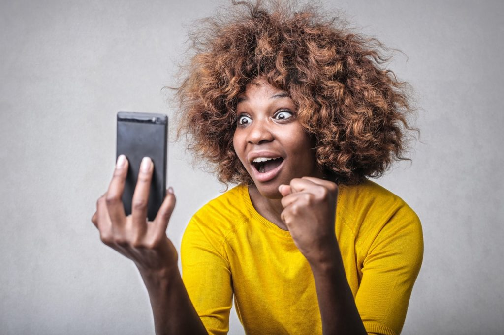 Woman reacting to a viral video on her cell phone